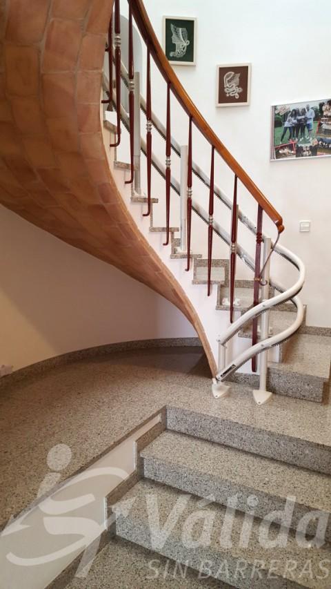 Escala de cargol amb cadira pujaescales per a pujar i baixar al pis superior en Palamós