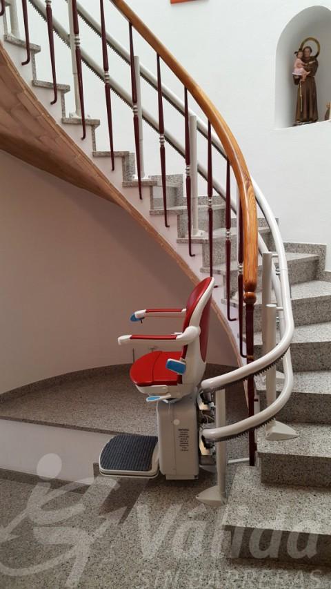 Escalera de caracol con silla subeescaleras roja en Palamós